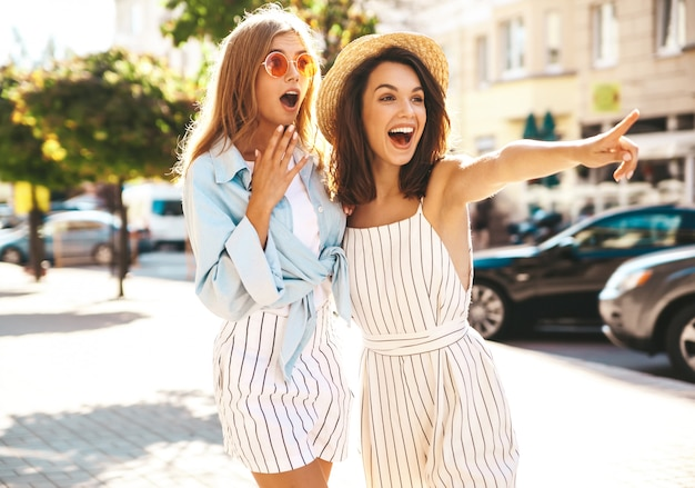 Two fashion young stylish hippie brunette and blond women models in summer sunny day in hipster clothes posing on the street background. pointing on shop sales