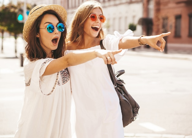 Two fashion young stylish hippie brunette and blond women models in summer sunny day in white hipster clothes posing . pointing on shop sales