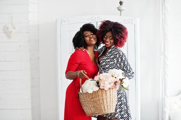 白い部屋で古いヴィンテージのワードローブに対して手に花のバスケットに立っているイブニングドレスで2つのファッショナブルなアフリカ系アメリカ人女性。