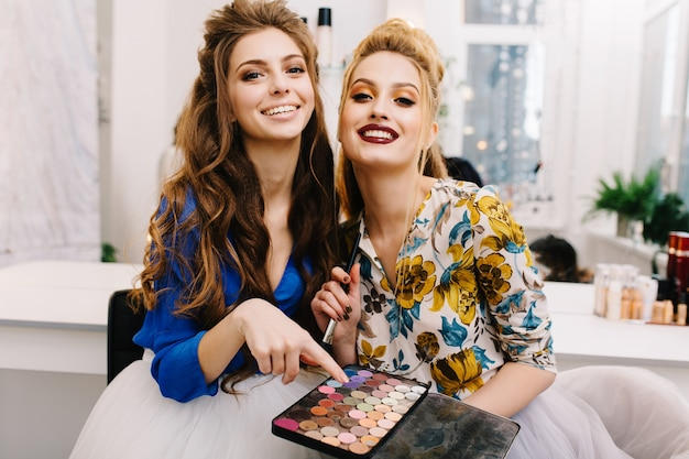 Two fashionable attractive models with stylish makeup, luxury coiffure having fun together in haidresser salon