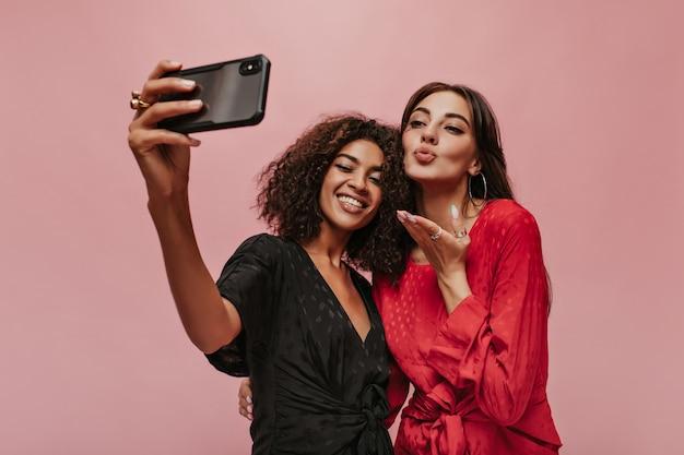 Due amici alla moda con i capelli scuri in abiti alla moda a pois che fanno selfie, sorridono e si baciano sul muro rosa pink