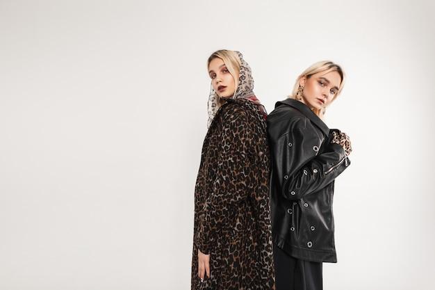 특대 유행의 청춘 옷을 입은 두 명의 유행하는 여자 친구가 서로 등을 맞대고 서 있습니다.
