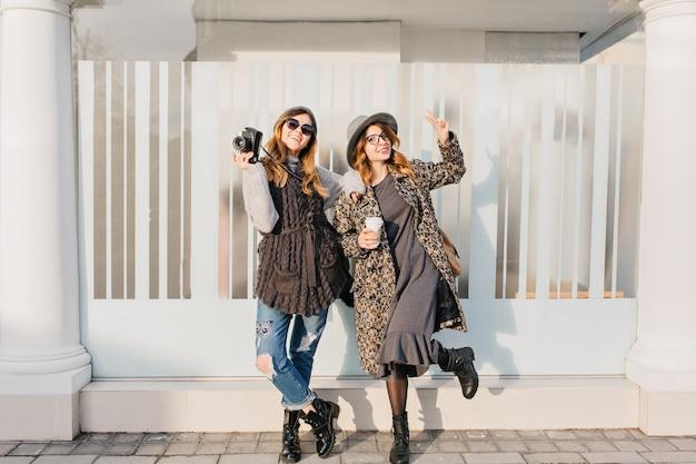 Две модные радостные улыбающиеся женщины веселятся на солнечной улице города. стильный образ, совместное путешествие, современная модная одежда, прогулки с кофе на вынос, выражение положительных эмоций.