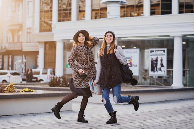 Due donne sorridenti gioiose alla moda che saltano sopra la città. look elegante, viaggiare insieme, indossare abiti di tendenza moderni, camminare con il caffè da asporto, esprimere emozioni positive.
