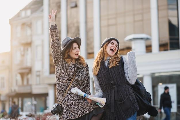 Две модные радостные улыбающиеся женщины перепрыгивают через город. стильный образ, совместное путешествие, современная модная одежда, прогулки с кофе на вынос, выражение положительных эмоций.