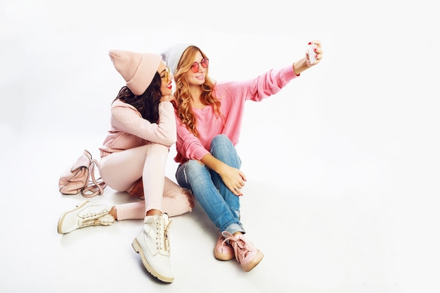 Two fashionable miling girls making self portrait. white background. pink  clothes.
