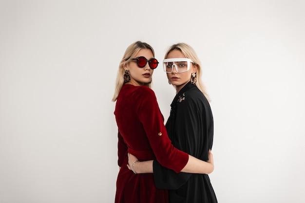 灰色の壁の近くのスタイリッシュなトレンディなビンテージ ドレスにサングラスを掛けた 2 人のファッショナブルな双子の姉妹
