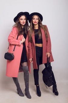Two fashionable young women in casual trendy spring coat, boots with heels, black hat and stylish handbag