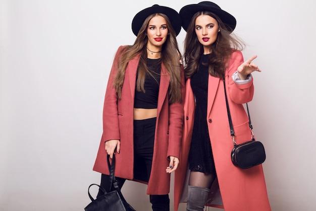 カジュアルなトレンディな春のコート、かかとのブーツ、黒い帽子、スタイリッシュなハンドバッグの2人のファッショナブルな若い女性