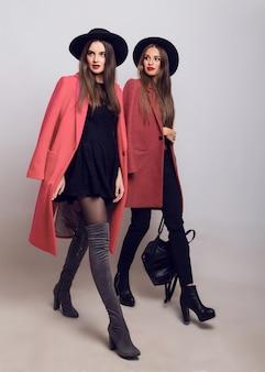 Две модные девушки в повседневном модном весеннем пальто, сапогах на каблуке, черной шляпе и стильной сумочке