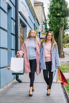 Two fashionable young women walk in fur coat walking on street holding shopping bags