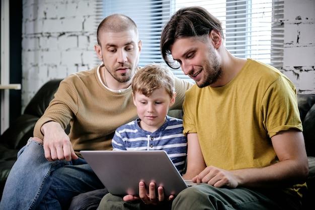 Два отца и их малолетний сын проводят время вместе дома и смотрят фильм или играют на ноутбуке