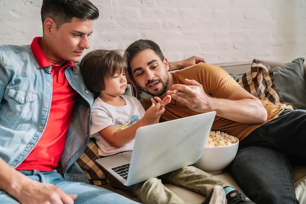 Двое отцов любят смотреть фильмы со своим сыном дома.