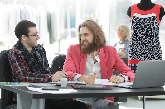 책상에 앉아 두 동료 디자이너