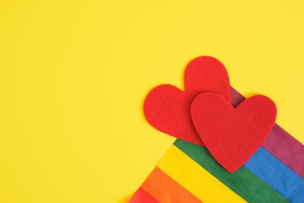 Two felt hearts ans lgbt rainbow colors flag on yellow background, free love and pride concept
