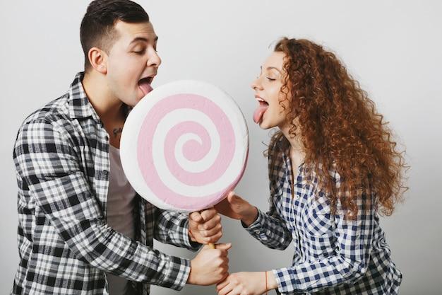 Две подруги женского пола и мужчины облизывают большой леденец, как сладости и конфеты, будучи сладким зубом, изолированным над белой стеной