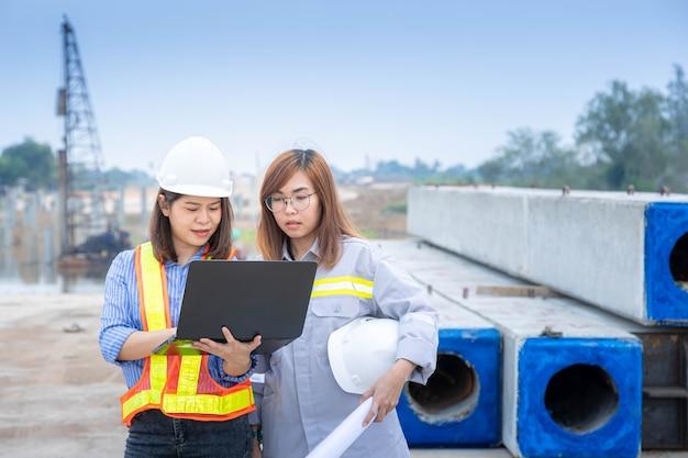 建設現場または建築現場でラップトップと青写真を扱う2人の女性建築家リーダー。