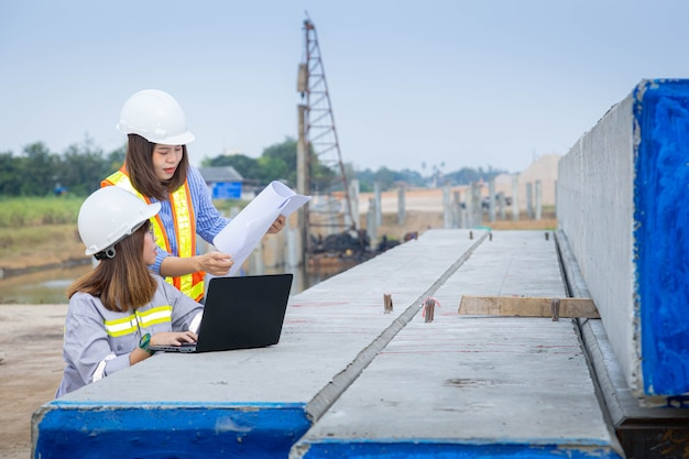 Two female architect leader working with laptop and blueprints at construction site or building site