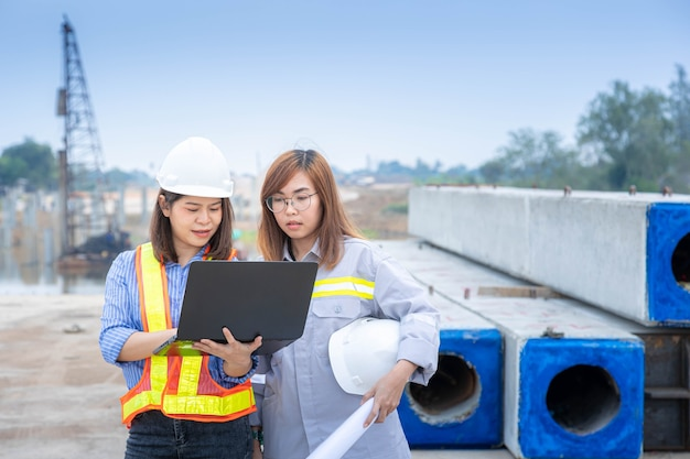 Two female architect leader working with laptop and blueprints at construction site or building site.