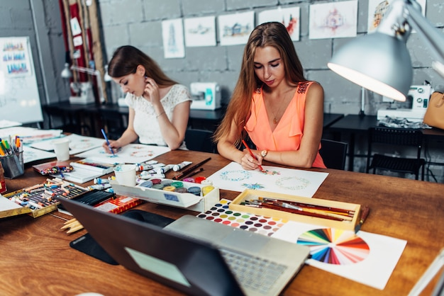 Two female artists drawing decorative elements sitting at desk in creative studio