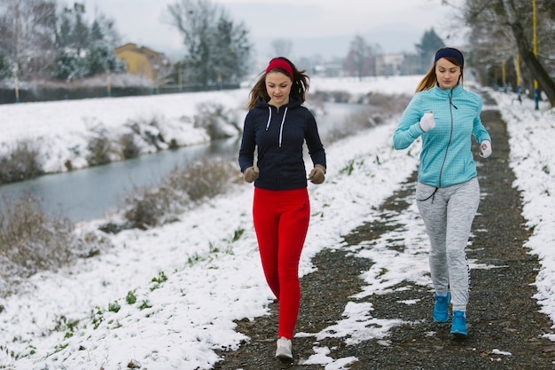 Two female athlete jogging on street near the river in winter