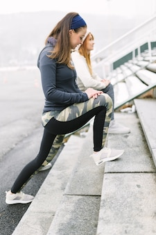 Two female athlete stretching her leg on steps