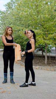 Две спортсменки остывают после тренировки, вытираются полотенцем и пьют свежую воду из бутылки