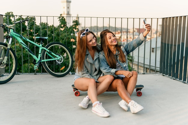 Two female best friends taking selfie with smartphone when sitting on skateboarding while walking at summer sunny day. outdoors.