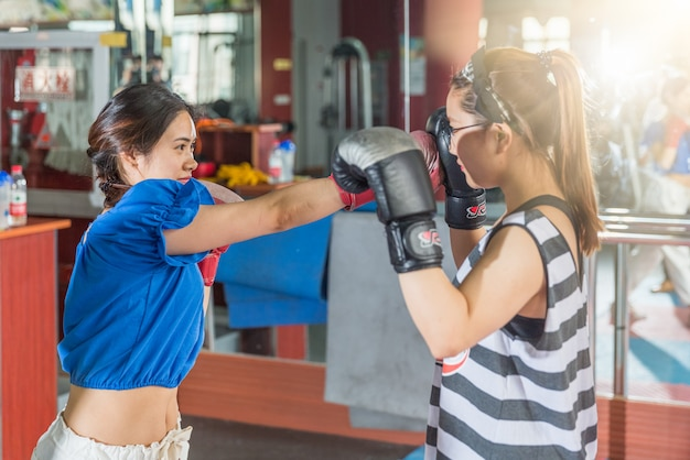 Two female boxing friends exercising in gymnasium.