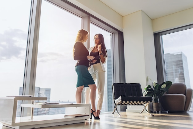 Two female business partners discussing plans standing in modern office at tower block.