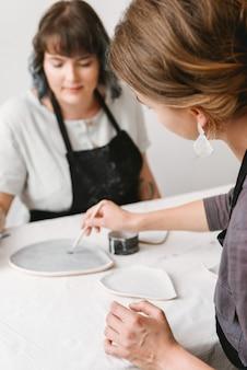 陶芸工房で手作業をしている2人の女性陶芸家。