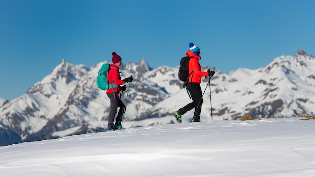 Two female climbers during a training walk on the snow