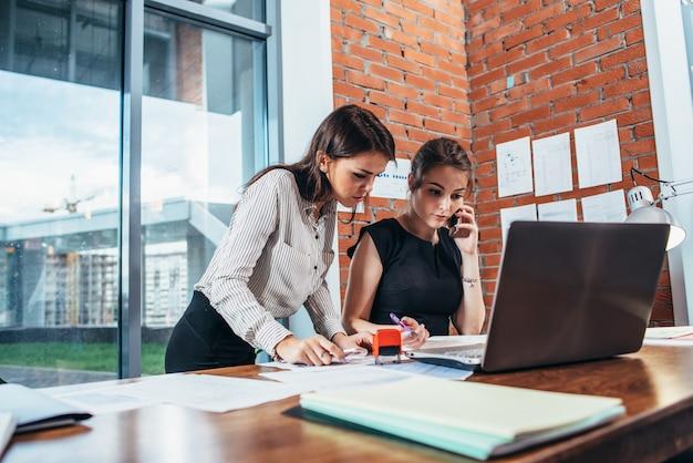 一緒に働いているオフィスの2人の女性の同僚。