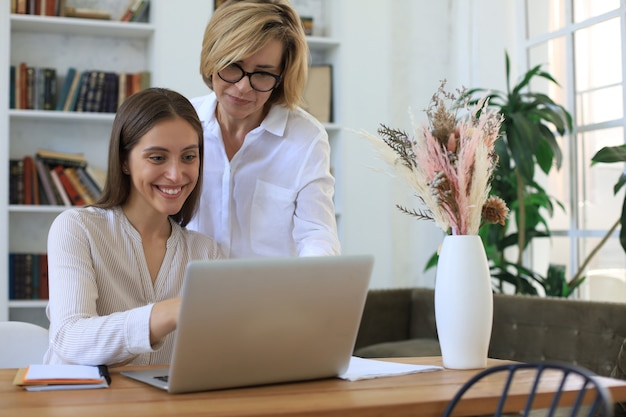 Две женщины-коллеги работают с ноутбуком и обсуждают новый проект.