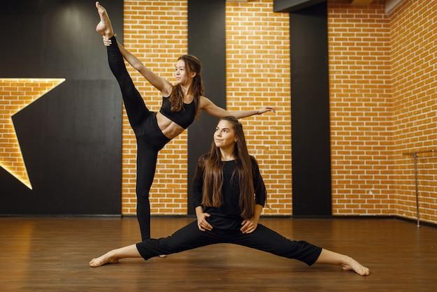 スタジオで2人の女性のコンテンポラリーダンスパフォーマー。クラスでのダンサーのトレーニング、モダンエレガンスダンス、ストレッチ体操