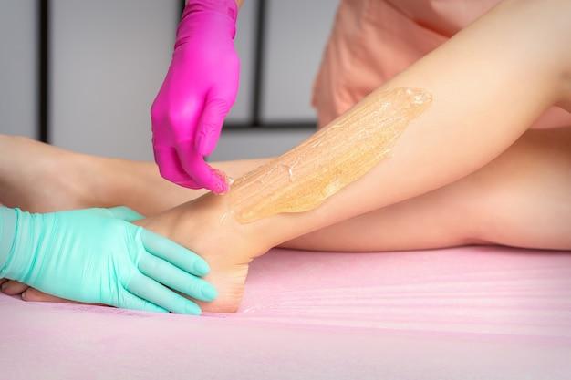 Две женщины-косметологи натирают женские ноги горячей сахарной пастой в салоне красоты