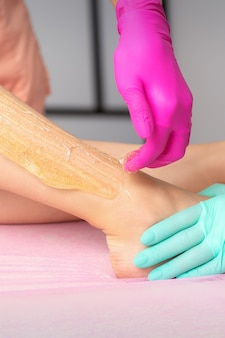 ビューティースパサロンでホットシュガーペーストで女性の足にワックスをかける2人の女性美容師