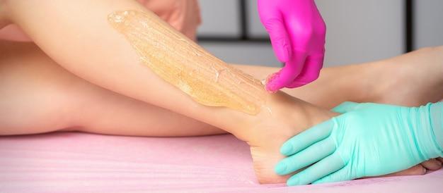 뷰티 스파 살롱에서 뜨거운 설탕 페이스트로 여자의 다리를 왁싱 두 여성 미용사