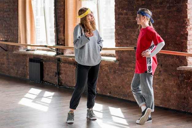 Two female dancer standing in the studio talking to each other