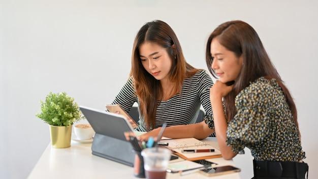 영감을 찾기 위해 휴대용 태블릿을 사용하여 아이디어를 공유하는 두 명의 여성 디자이너