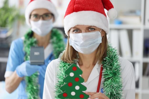 Две женщины-доктора в защитных медицинских масках и шляпах санта-клауса улыбаются