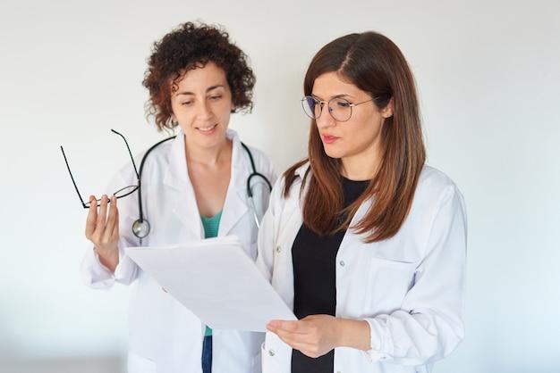 Две женщины-доктора просматривают документы и обсуждают диагноз