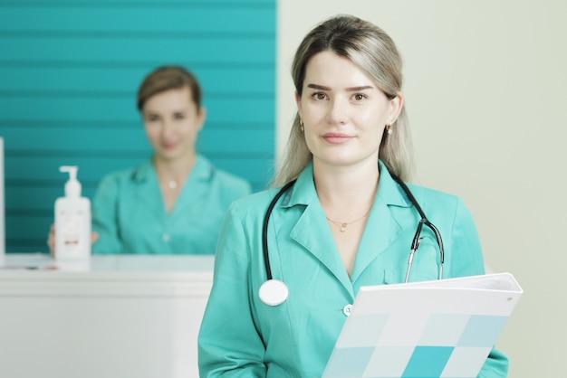 Две женщины-доктора или медсестры позируют. фонендоскоп стетоскоп на шее. в руках держит папку