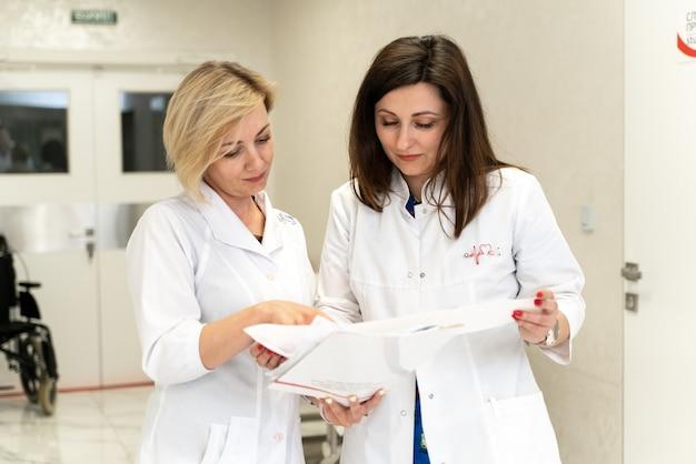 病院に立って、話し、書類を見ている2人の女性医師。仕事について話し合い、紙の上で見ている女性医師