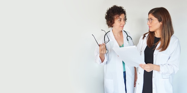 Two female doctors talk about some documents on isolated white background