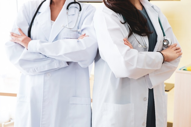 Two female doctors with headphones standing in hospital.