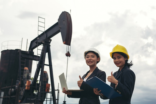 Two female engineers stand beside working oil pumps with a white sky .