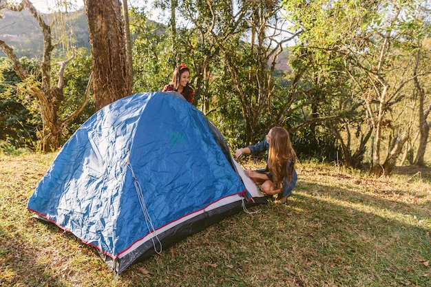 Two female friend setting tent while camping in forest