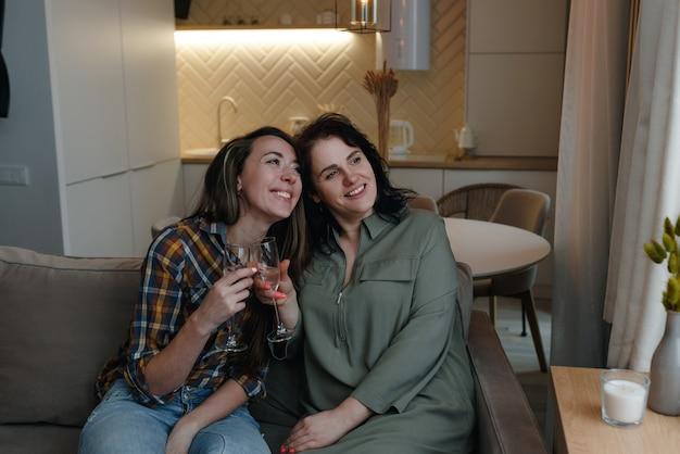 두 여자 친구가 소파에 앉아 안경을 들고 창 밖을 내다보고 있습니다.