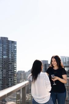 옥상 테라스에서 와인을 마시며 대화를 나누는 두 여자 친구